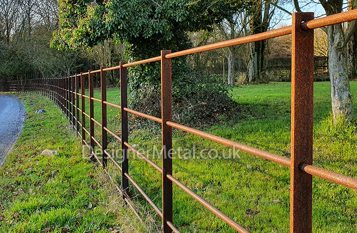 Natural rust finish estate fencing in a countryside setting.