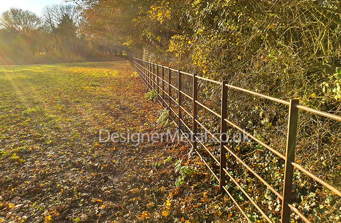 A line of estate fencing in rust finish installed in Suffolk.